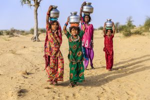 Indian little girls crossing sand dunes and carrying on their heads water from local well, Thar Desert, Rajasthan, India. Rajasthani women and children often walk long distances through the desert to bring back jugs of water that they carry on their heads.